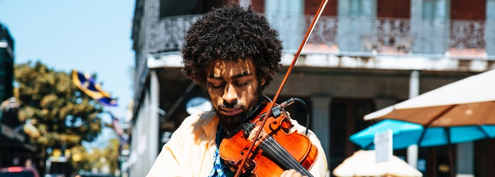 A young man playing the violin in the street