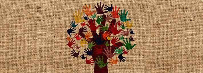 A tree with the trunk and branches formed by a hand, supporting leaves made from multi-coloured hands