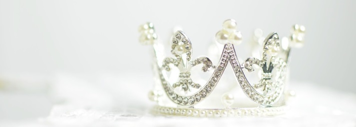 A silver crown against a blurred white and grey background