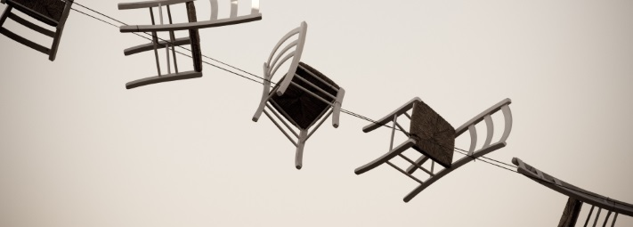 A row of chairs suspended from some wires in mid air