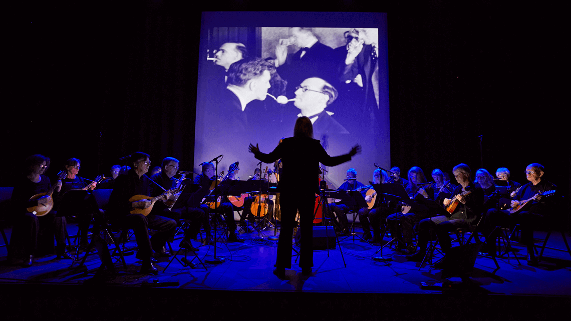 silhouette of conductor and mandolin group performing in front of big screen of archive footage