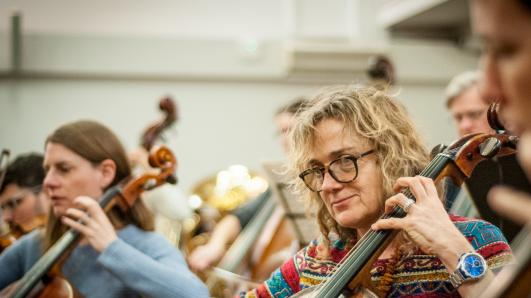 close up of a woman playing a cello with others in rehearsal