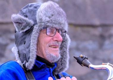 A member of Aberdeenshire Saxophone Orchestra smiles with his instrument, wrapped up warm for an outdoor rehearsal