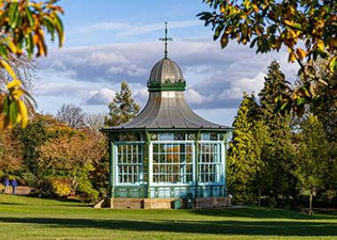 A bandstand is bathed in sunlight under a blue sky, surrounded by leafy greenery in a park