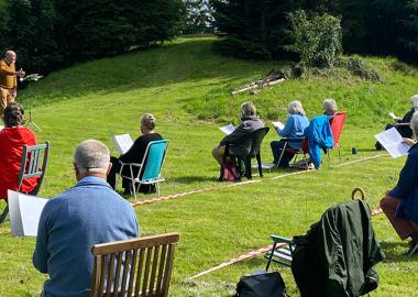 choir rehearses outdoors in green space with social distancing measures