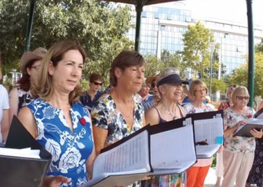 A female choir stand in line on tour, holding manuscripts to read from