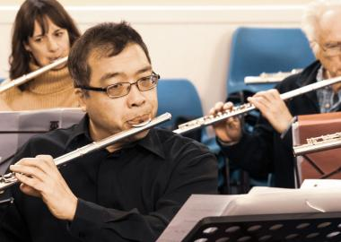 people arranged in seated rows playing the flute together in a community hall