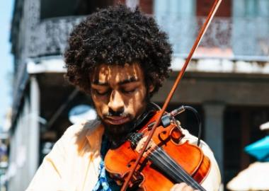 a young man playing the violin outdoors