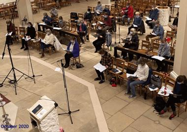 choir members sit socially distanced in church with masks in rehearsal October 2020