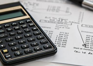 calculator on top of sheet of accounts and notes