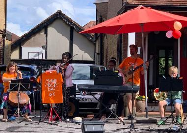 Five members of The Penton Road Band performing in a driveway in Staines, Surrey, as part of Make Music Day 2020