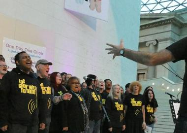 Choir With No Name wearing choir t shirts, singing in the British Museum Great Court, musical director conducting