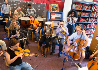 People gathered in a music library space playing orchestral instruments, smiling