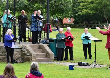 Cantiones Choir perform outdoors on a bandstand