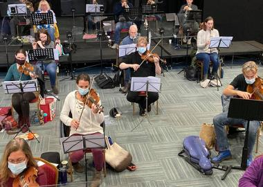The film Orchestra rehearse, masked and socially distanced