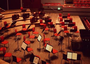 Red chairs and music stands are assembled onstage for an orchestra