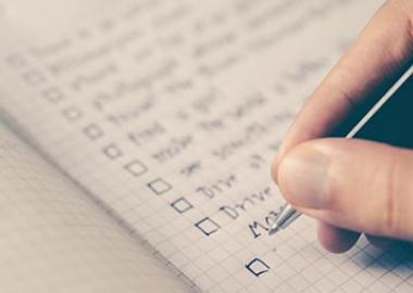 A hand holding a pen, poised over a notebook in which a checklist is written